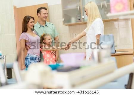 Little girl and her parents visiting dentist. The little girl is shaking hand with female dentist and smiling.