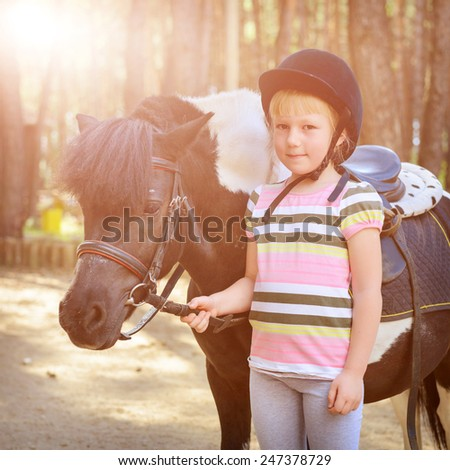 Little girl and her pony. Filtered image - stock photo