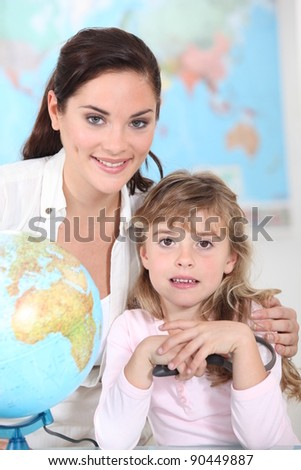 little girl and her teacher posing together - stock photo