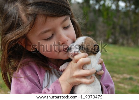 little girl and her very young puppy purebred jack russel terrier - stock photo