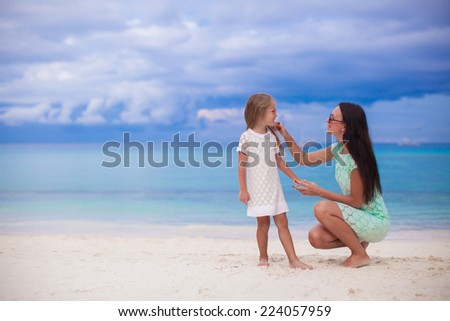 Little girl and her young mother relax at the beach