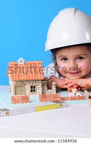 Little girl and house under construction - stock photo