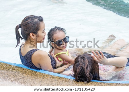 Little girl and ladies relaxing at the edge of a swimming pool.