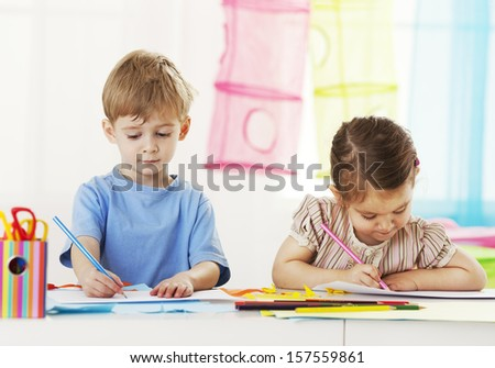 Little girl and little boy drawing - stock photo
