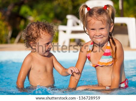little girl and little boy sitting  in the swimming  pool - stock photo