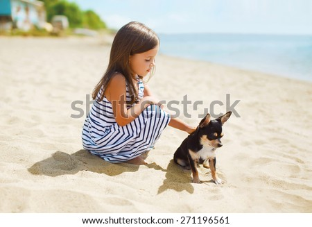 Little girl and little dog on the beach in sunny summer day near sea, child with puppy outdoors - stock photo