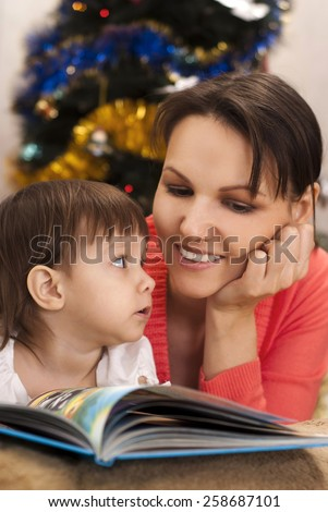 Little girl and mom sitting at a table with a book - stock photo