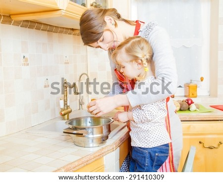 Little girl and mother cooking together in the kitchen. - stock photo