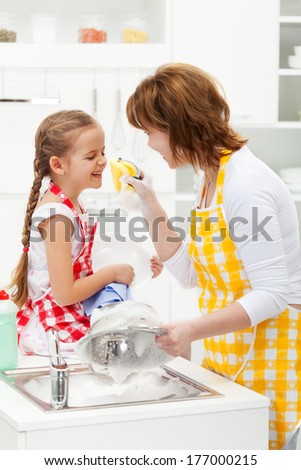 Little girl and mother having fun with the foam - washing the dishes together - stock photo