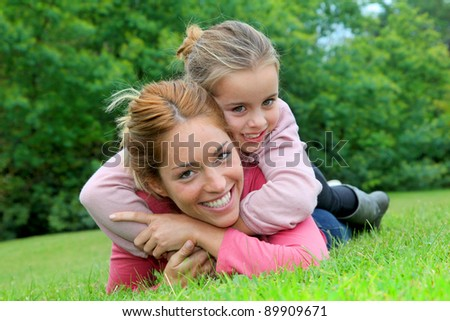 Little girl and mother laying on grass in park - stock photo