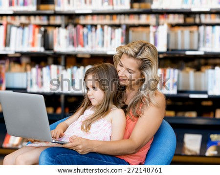 Little girl and mother with a laptop in library - stock photo
