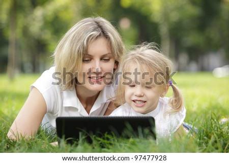 Little girl and mother with laptop outdoor - stock photo