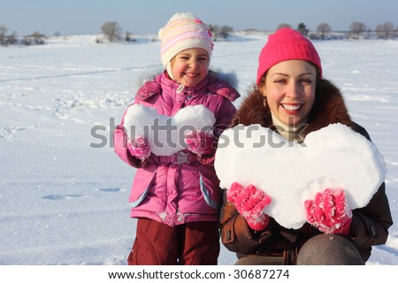Little girl and mother with snowy hearts - stock photo
