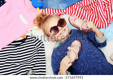 Little girl and new clothes, top view - stock photo