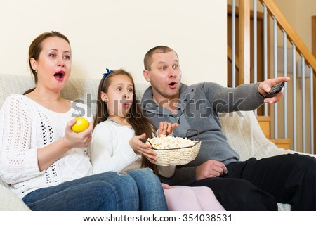 Little girl and parent sitting with popcorn in front of TV. Focus on woman - stock photo