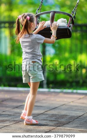 Little girl and seesaw in warm summer day - stock photo