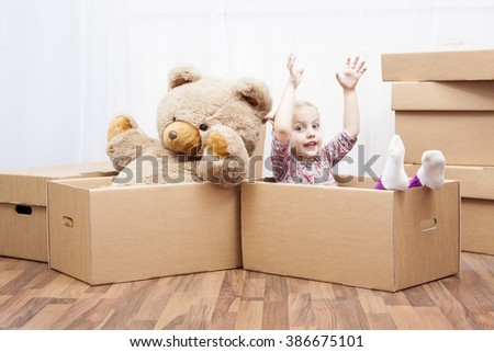 little girl and teddy bear in box, family in move - stock photo