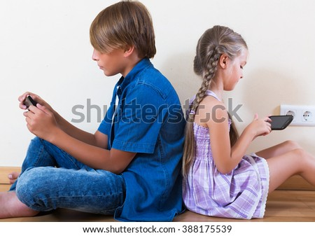 Little girl and teenage boy playing in mobile phones at home - stock photo