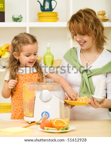 Little girl and woman making fresh orange juice - healthy life concept - stock photo