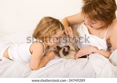 Little girl and woman playing with a kitten laying on the bed