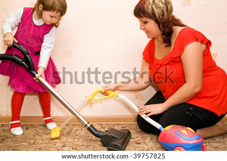 Little Girl and woman vacuum a carpet - stock photo