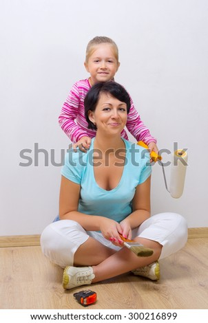Little girl and woman with working tools - stock photo