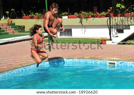 Little girl and young boy jumping in pool - stock photo
