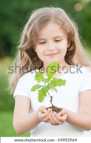 Little girl and young plant of a oak - stock photo