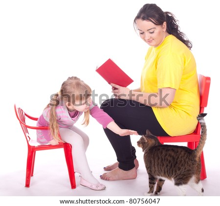 little girl and young woman with book and cat - stock photo