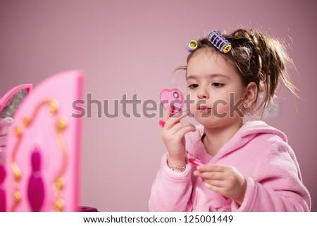 Little girl applying toy lipstick - stock photo