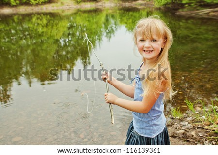 Little girl are fishing on lake in forest - stock photo