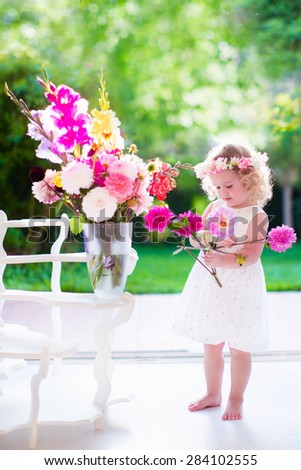 Little girl arranging flowers at home in a vase. Child playing indoors. Kids birthday party. Children giving flower as present. Kid in a living room with big window and door to the garden. Summer fun. - stock photo