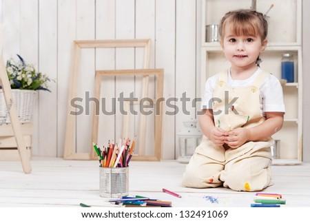 Little girl artist paints in his studio - stock photo