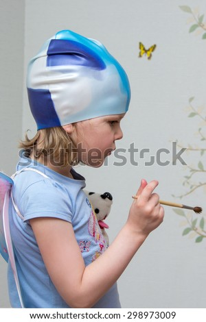 Little girl artist with a brush in hand in a rubber cap - stock photo