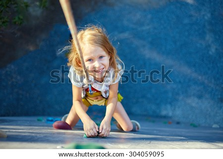 Little girl ascending in outdoor rock climbing gym - stock photo