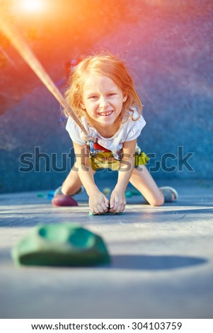 Little girl ascending in outdoor rock climbing gym