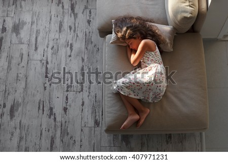 Little girl asleep on couch - stock photo