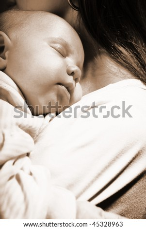 little girl asleep on mother's chest - stock photo