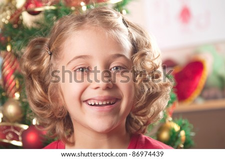little girl at a Christmas fir-tree. - stock photo