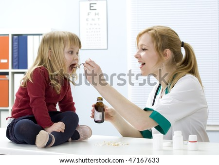 little girl at lady doctor drinks syrup - stock photo