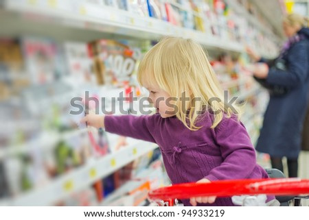 Little girl at magazines section in supermarket - stock photo