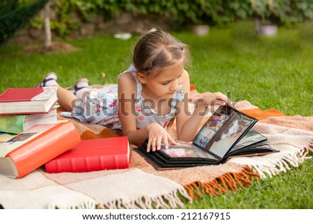 Little girl at park looking at family photo album - stock photo