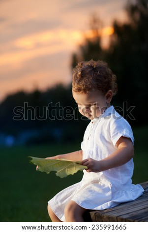 Little girl at sunset. Cute girl in the park - stock photo