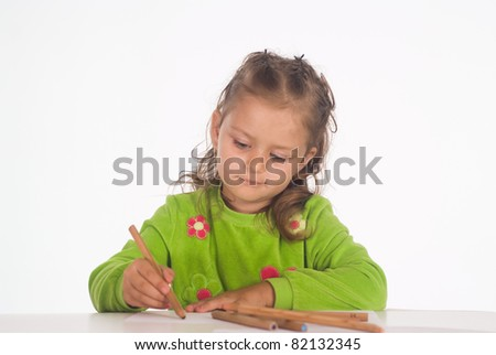 little girl at table drawing on a white - stock photo