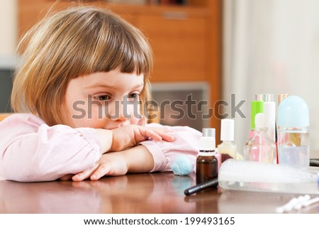 little girl at  table with cosmetic products