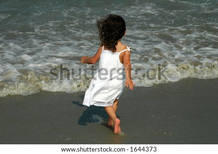 Little girl at the beach - stock photo