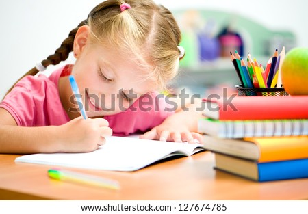 little girl at the desk is writing