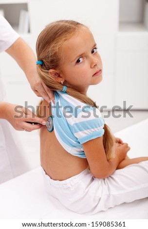 Little girl at the doctor for an examination - being checked with a stethoscope