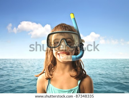 Little girl at the seaside wearing a diving mask - stock photo