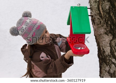 Little girl attaches bird feeder to a tree in winter - stock photo